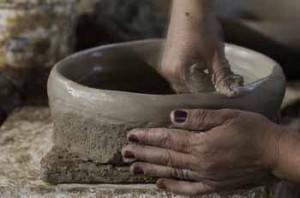 mãos de mulher fazendo panela de barro