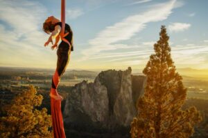 Smith Rock, Oregon, USA --- Woman performing on aerial silks at Smith Rock at sunset --- Image by © Isaac Lane Koval/Corbis