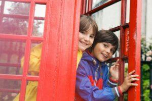 London, England, UK --- Children (10-12) playing in Telephone Box, London, England, UK --- Image by © Emma Tunbridge/Corbis