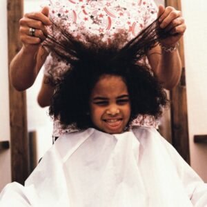Hairstylist Pulling Girl's Hair --- Image by © Image Source/Corbis