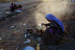 07 Aug 2014, Dohuk, Iraq --- A woman prepares a meal for her family in a camp in Dohuk, Iraq on Aug. 7, 2014. This camp, formerly for Syrian refugees, has now had the Yazidi minorities transfered to it. Yazidi families have retreated to escape the killings of Yazidis by the militant group Islamic State of Iraq and Syria, ISIS. --- Image by © Ali Arkady/VII Mentor Program/Corbis