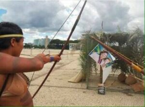Índio fazendo mira no cartaz Kátia e Dilma em Palmas